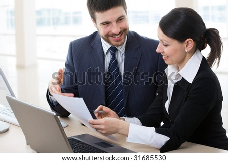 Two business people discussing a document in a modern office.