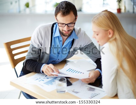 Two business people discussing documents at meeting  - stock photo