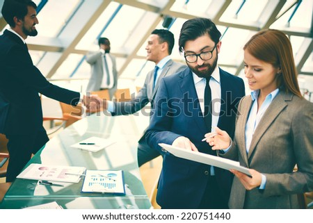 Two business people discussing paper on background of their colleagues handshaking in office - stock photo