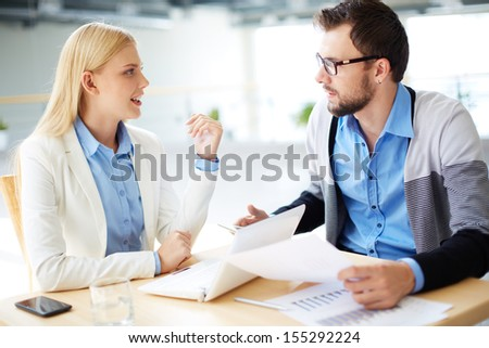 Two business people discussing plans or project at meeting