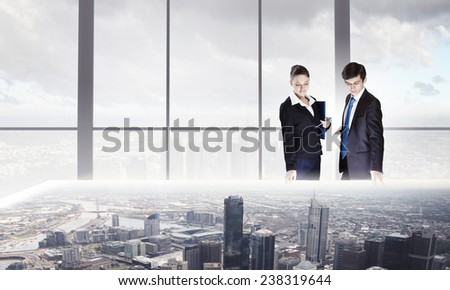 Two business people examining design of construction model