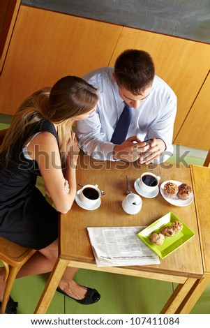 Two business people having a break in caf�© and looking at a smartphone - stock photo