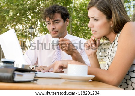 Two business people having a meeting and using technology outdoors, while having a coffee in a coffee shop terrace. - stock photo