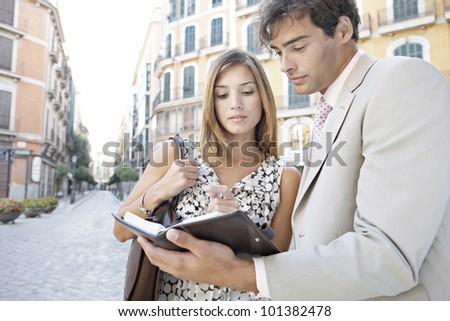 Two business people having a meeting in the city, outdoors. - stock photo