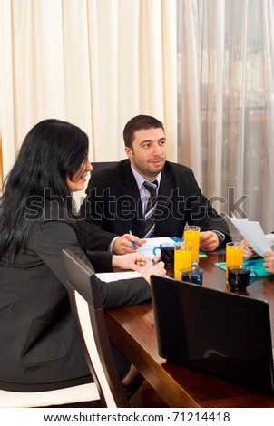 Two business people having discussion with others at meeting - stock photo