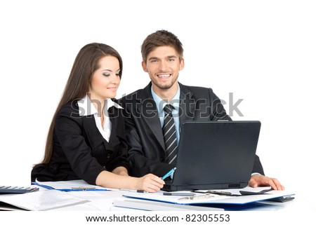 Two business people in elegant suits sitting at desk working in team together, discussing the problem, working on laptop, papers, document, looking at camera, Isolated over white background