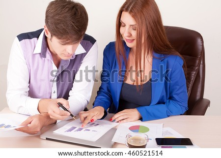 Two business people in elegant suits sitting at desk working in team together with documents sign up contract, holding clipboard, folder with papers, business plan.