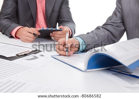 Two business people in elegant suits sitting at desk working in team together with documents sign up contract, holding clipboard, folder with papers, business plan. Isolated over white background.