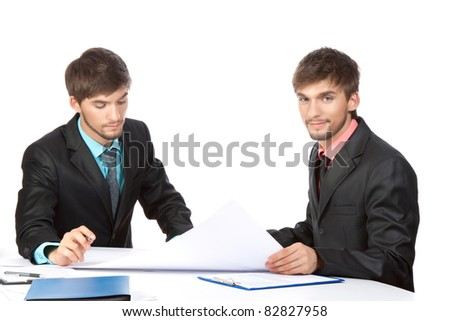 Two business people in elegant suits sitting at desk working in team together, working with documents sign up contract, blueprint, folder with papers, business plan. Isolated over white background.