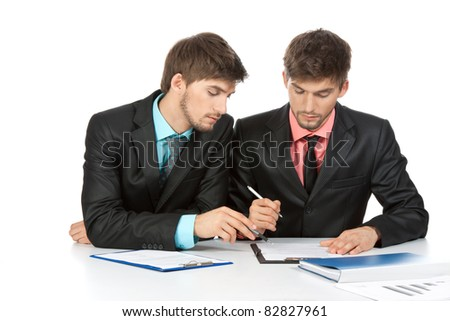 Two business people in elegant suits sitting at desk working in team together, working with documents sign up contract, on clipboard, folder with papers, business plan. Isolated over white background - stock photo