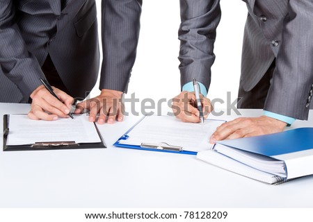 Two business people in elegant suits standing at desk working in team together, working with documents sign up contract, clipboard, folder with papers, business plan. Isolated over white background.