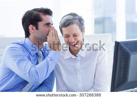 Two business people looking at a paper while working on computer in the office - stock photo
