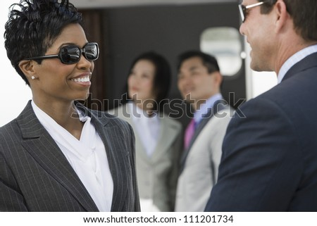 Two business people looking each other with colleagues in the background - stock photo