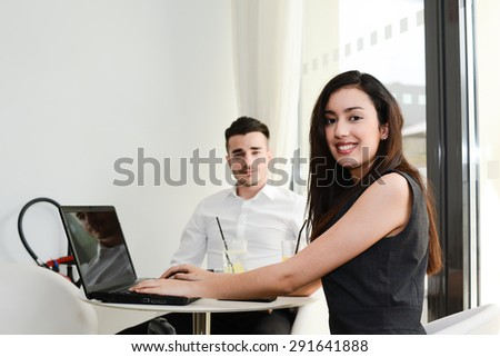 two business people man and woman working on computer while waiting in an airport lounge - stock photo