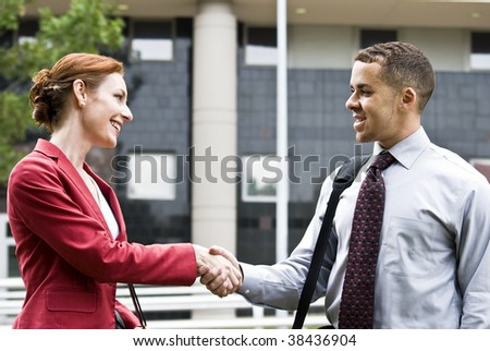 Two business people outside a downtown building greeting each other with a handshake.