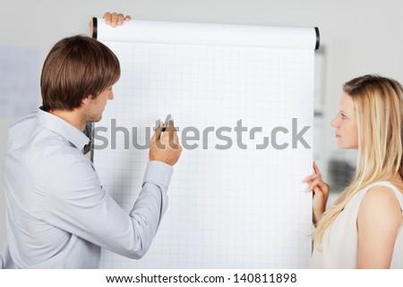 two business people preparing presentation at flipchart - stock photo