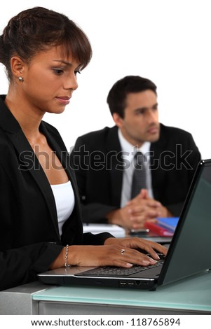 Two business people sat next to each other - stock photo