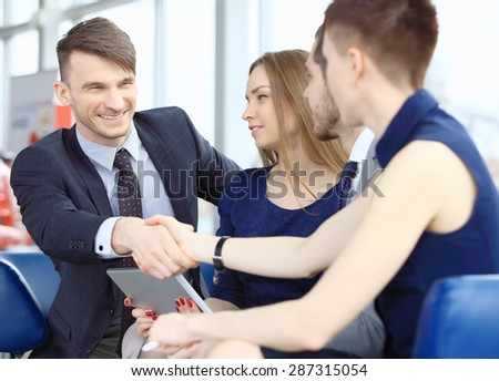 Two business people shaking hands as successful agreement in real estate agency office - stock photo