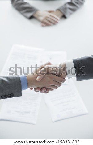 Two business people shaking hands over table