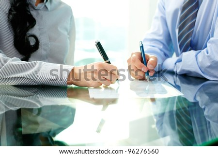 Two business people signing a document - stock photo