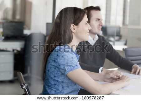Two business people sitting at conference table and listening during business meeting