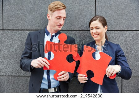 Two business people solving big red jigsaw puzzle pieces - stock photo