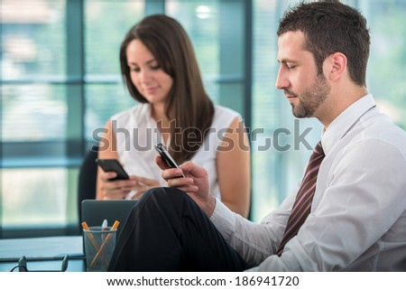 Two business people texting in modern office environment