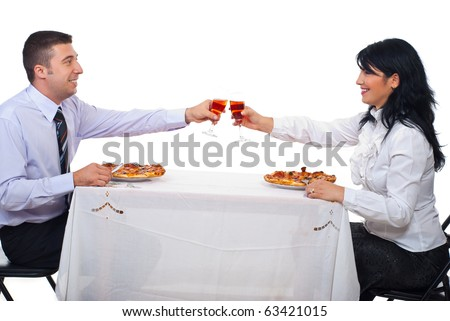 Two business  people  toasting with wine and eating pizza at table