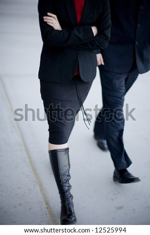 Two business people walking together fast