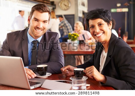 Two business people with laptop meeting in a coffee shop - stock photo