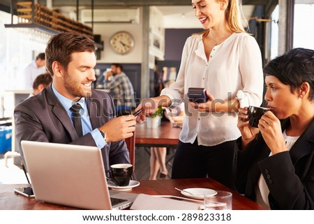 Two business people with laptop paying in a coffee shop - stock photo