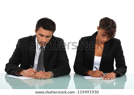 Two business people writing at a desk - stock photo