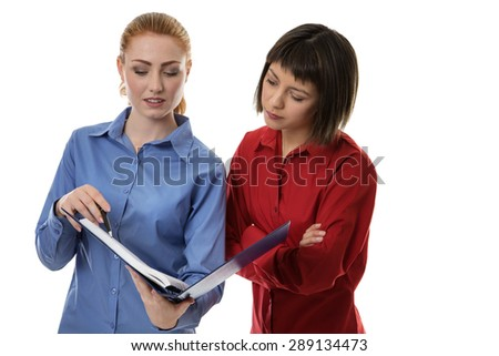 Two business woman chatting away together going over some notes