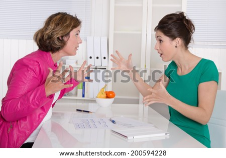Two business woman disputing in the office having disagreement. - stock photo