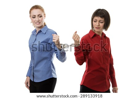 two business woman handcuffed together - stock photo