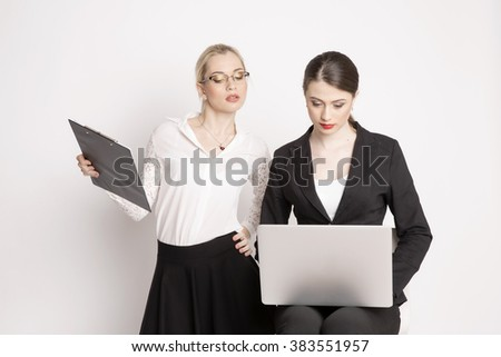 Two business woman on a white background. The business girl looks at the monitor and working.