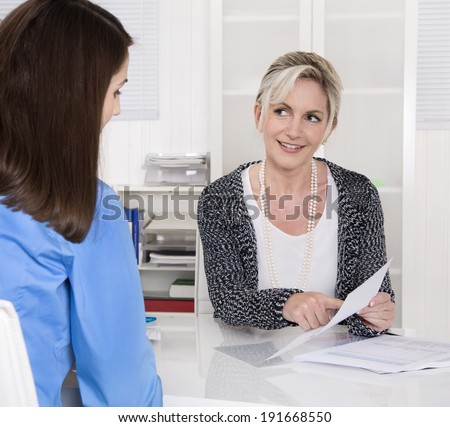 Two business woman sitting at desk in a meeting. - stock photo