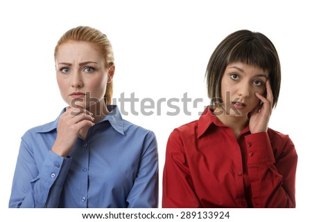 two business woman with different face expressions sanding side by side looking worried - stock photo