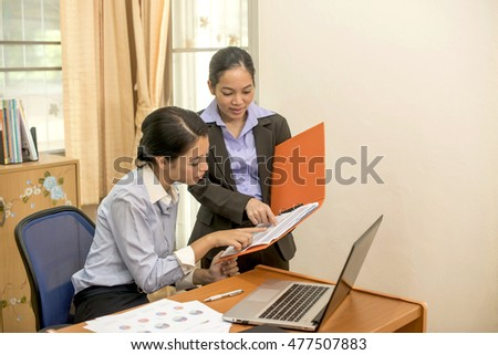 Two business women are checking financial reports .