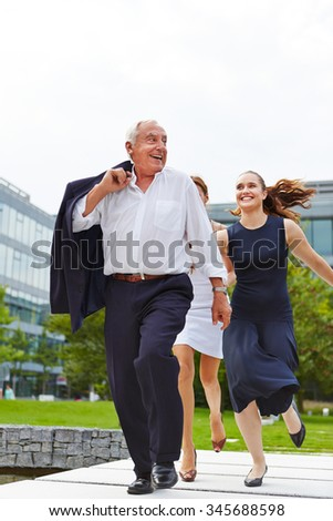 Two business women catching senior manager running away - stock photo
