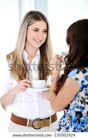 Two Business women enjoying a cup of coffee - stock photo