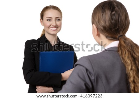 two business women having a conversation.  One is holding a blue folder.   Shot is taken from over one of the womens shoulder.  isolated on white