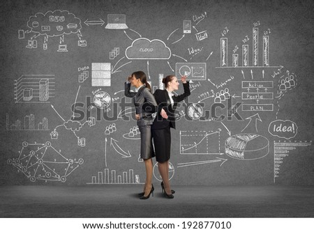two business women holding hands, looking in different directions, teamwork - stock photo
