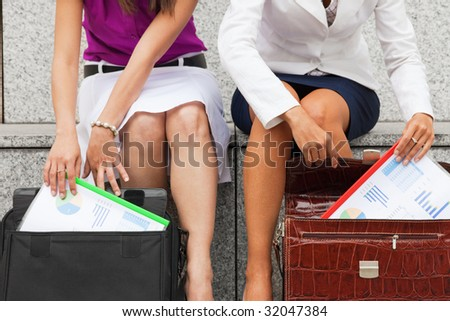 two business women meeting outdoors and holding budget reports - stock photo
