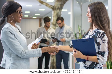 Two business women shaking hands at office with colleagues in the background.