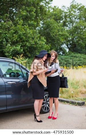 Two business women standing near the car, enter into an agreement on sale and purchase of the car. Stylish woman in the yard. Keys in hand