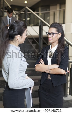 Two business women talking in front of stairs