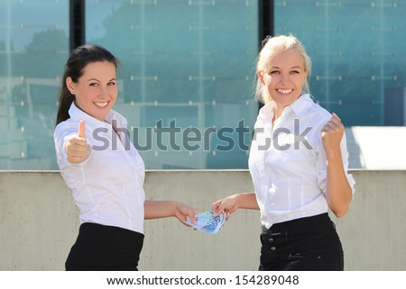 two business women thumbs up with euro banknotes over street background - stock photo