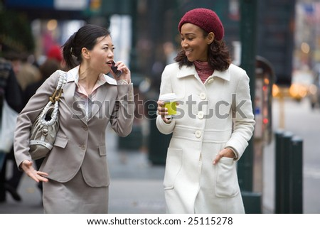 Two business women walking in the big city. One is on her cell phone. - stock photo