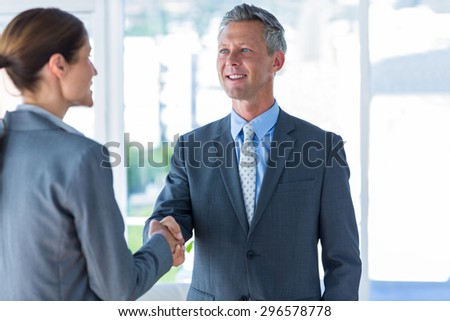 Two business workers shake hands in office